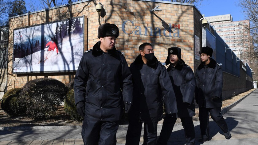 Chinese police patrol Wednesday in front of the Canadian Embassy in Beijing.