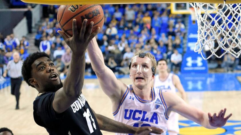 Colorado guard Namon Wright, left, shoots as UCLA center Thomas Welsh defends during the second half on Saturday. Colorado won 68-59.