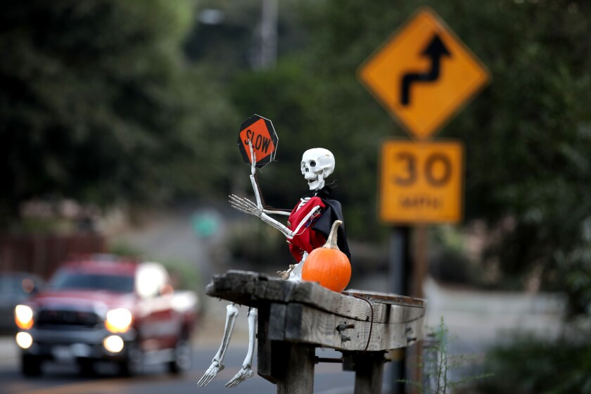 A skeleton perched on a bench encourages motorists to slow down on Carbon Canyon Road in Orange County.