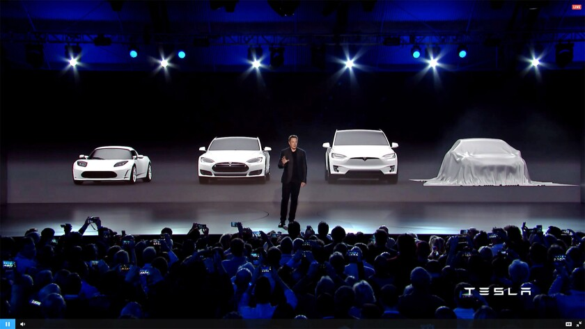 Elon Musk unveils Tesla's newest electric car, the Model 3, at the company's Hawthorne Design Studio on Thursday.
