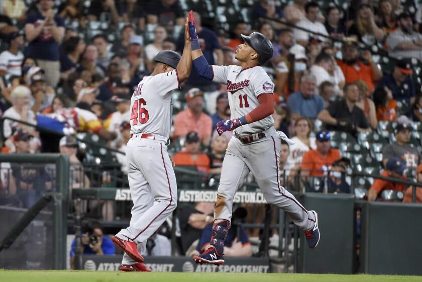 Minnesota Twins' Jorge Polanco, right, celebrates his three-run home run with third base coach Tony Diaz during the sixth inning of a baseball game against the Houston Astros, Sunday, Aug. 8, 2021, in Houston. (AP Photo/Eric Christian Smith)