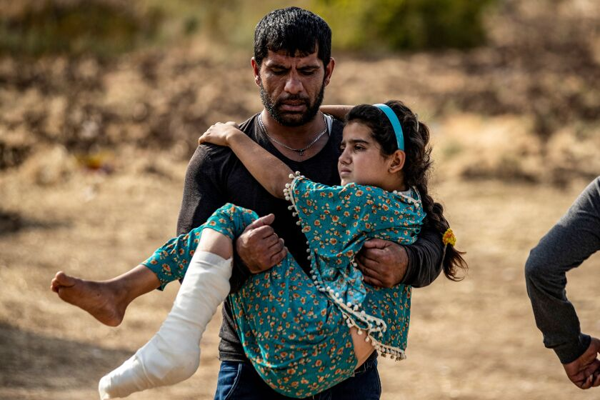 An injured Syrian Arab girl is carried away after receiving medical treatment last week at a hospital in Tal Tamr.