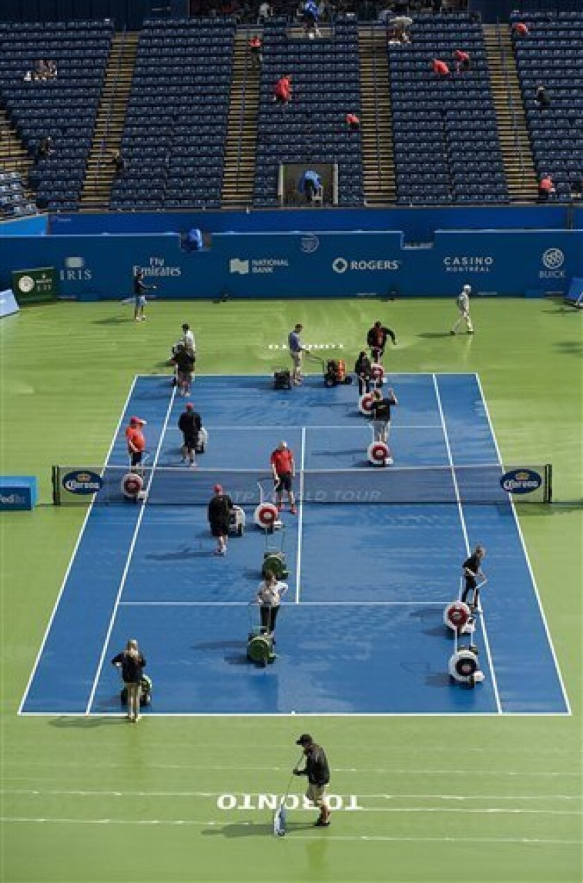 The sun shines as workers dry the court during a rain delay at the Rogers Cup tennis tournament in Toronto on Friday Aug. 10, 2012 in Montreal. (AP Photo/The Canadian Press, Paul Chiasson)
