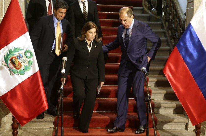 Russian's Foreign Minister Sergey Lavrov, right, helps Peru's Foreign Miniterv Eda Rivas before a joint press conference at the Foreign Ministry building in Lima, Peru, Wednesday, April 30, 2014. Lavrov is Lima, for a one day visit in his tour of Latin America. (AP Photo/Martin Mejia)