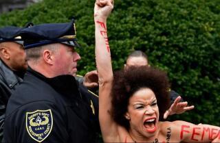 Una manifestante en topless se lanza sobre Bill Cosby cuando comienza un nuevo juicio