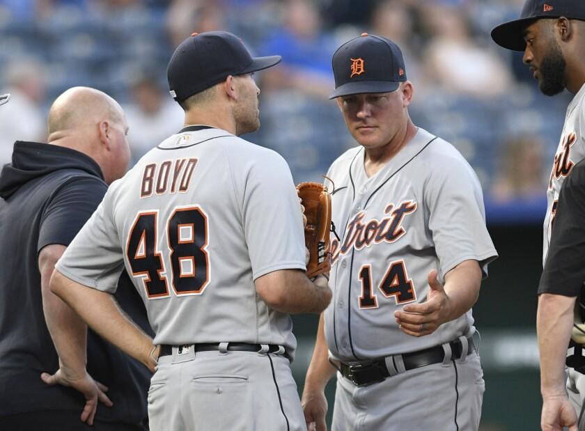 El pitcher abridor de los Tigres de Detroit Matthew Boyd (48) sale de su juego de béisbol tras hablar con el manager A.J. Hinch (14) en el tercer inning de su juego de béisbol contra los Reales de Kansas City, en Kansas City, Missouri, el lunes 14 de junio de 2021. (AP Foto/Reed Hoffmann)