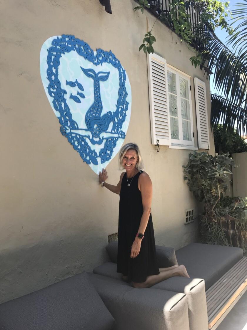 Artist Annika Nelson with a mermaid art installation.