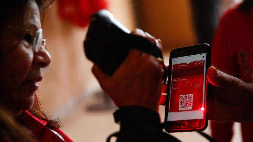 ANAHEIM, CALIF. - APRIL 04: Genevieve Hyland, of Anaheim, scans a ticket displayed on the screen of