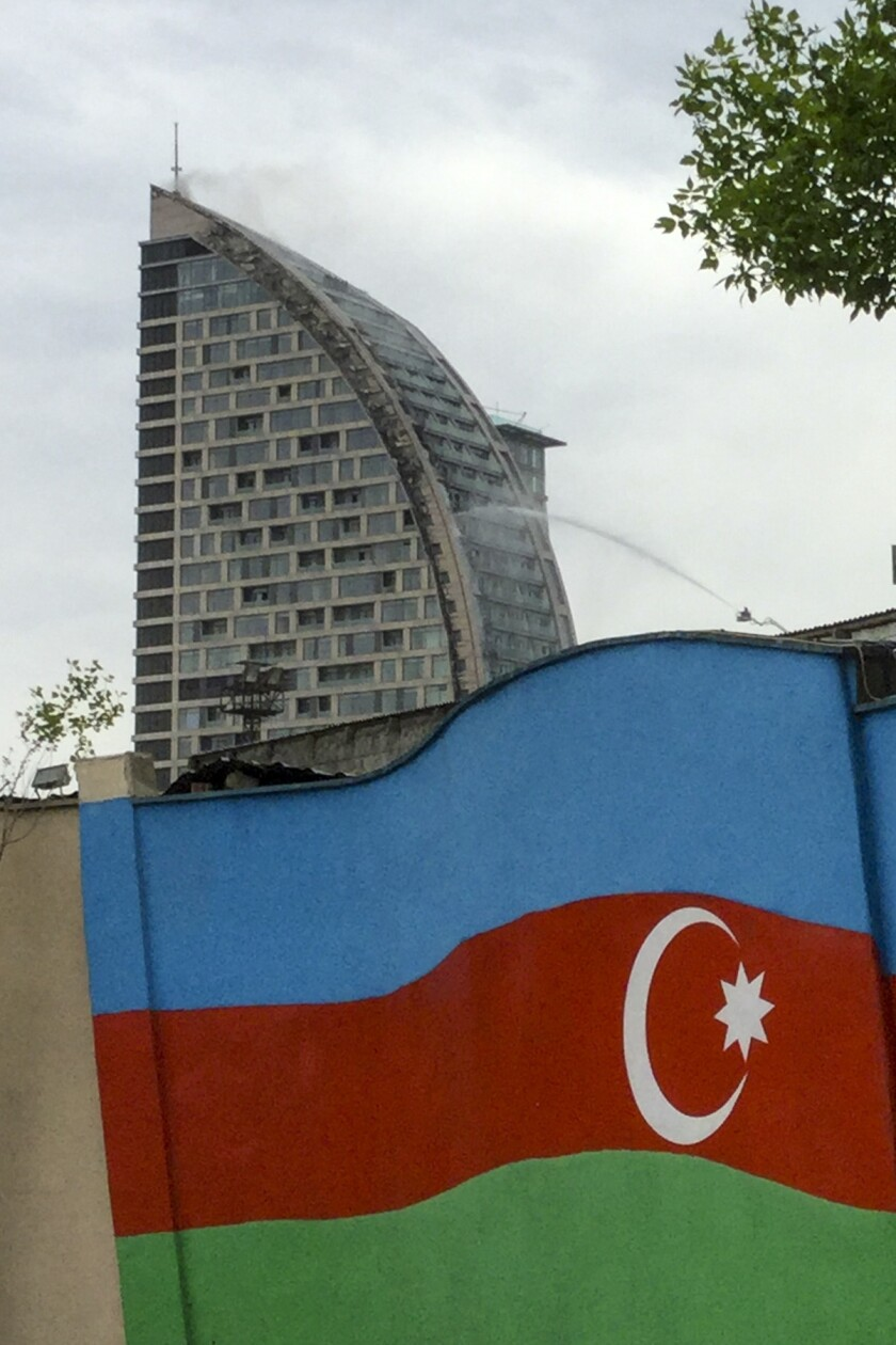 Azerbaijani firefighters on Saturday douse a fire at a building in Baku, Azerbaijan, that was once intended to be a Trump-branded hotel.
