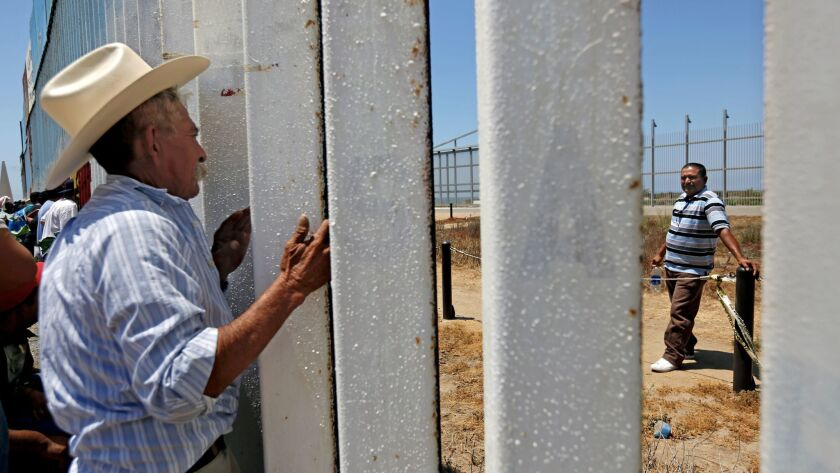 Mauro Mejia, 63, of Nayarit, Mexico, peers through the fence at the beach in Tijuana, to visit with his son Ricardo Mejia, 44, right, of Riverside, whom he had not seen in 25 years.