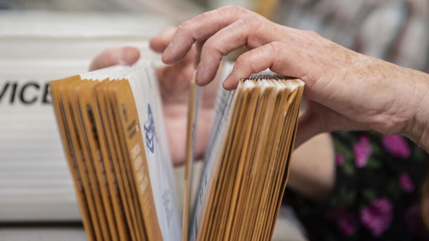 An employee of the Orange County Registrar of Voters sorts through mail-in ballots on Wednesday, Nov