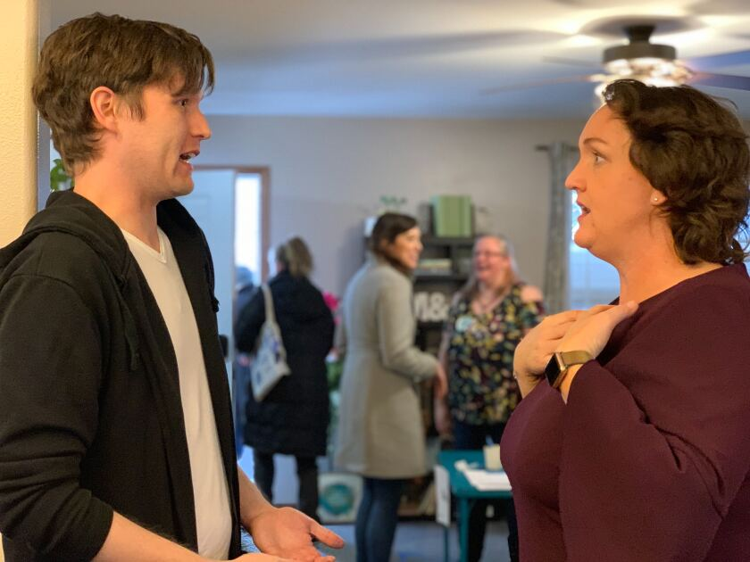 Rep. Katie Porter of Irvine speaks with voter Matthew Neppel at a campaign gathering in Cedar Rapids, Iowa, in January.