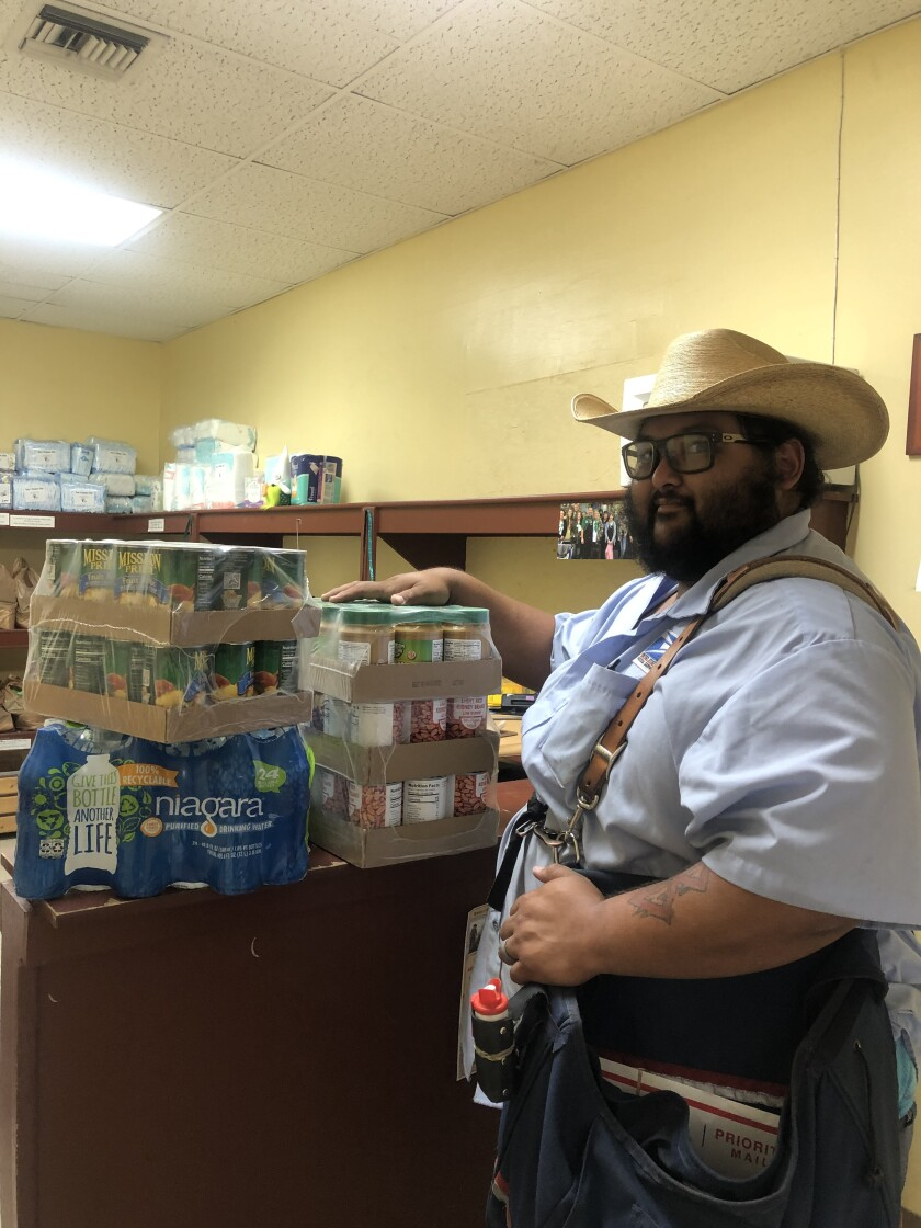 Ramona Food and Clothes Closet's letter carrier, Drew Pittman, with some food for RFCC.