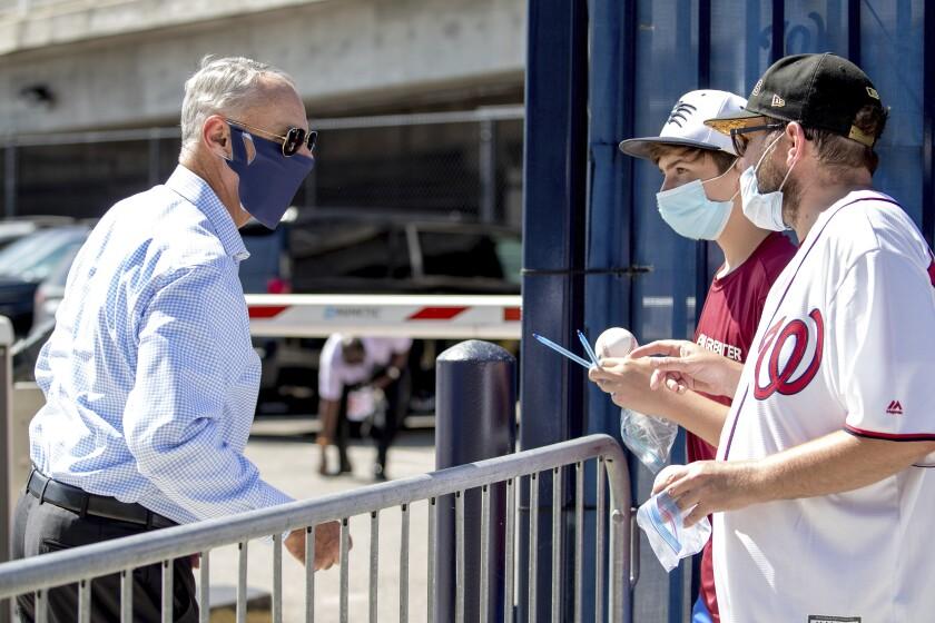 Rob Manfred, comisionado de las Grandes Ligas, habla con un par de fanáticos, a su llegada al Nationals Park de Washington, el jueves 23 de julio de 2020 (AP Foto/Andrew Harnik)