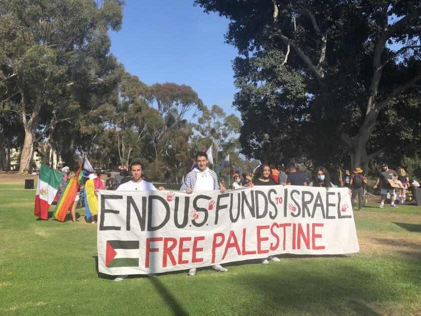 """Members of the """"Free Palestine"""" movement hold up a sign during the rally."""
