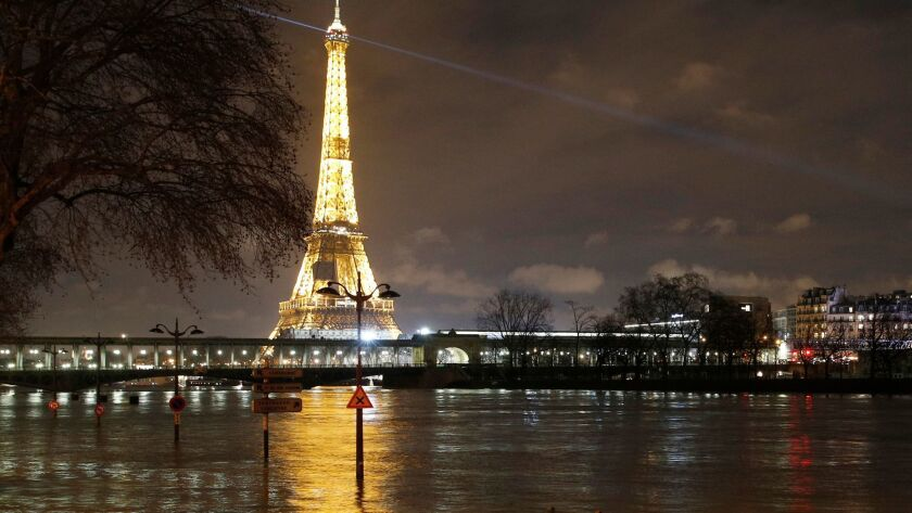 Streetlamps and signboards serve as markers for floodwater levels next to the River Seine in Paris on Jan. 27, 2018.