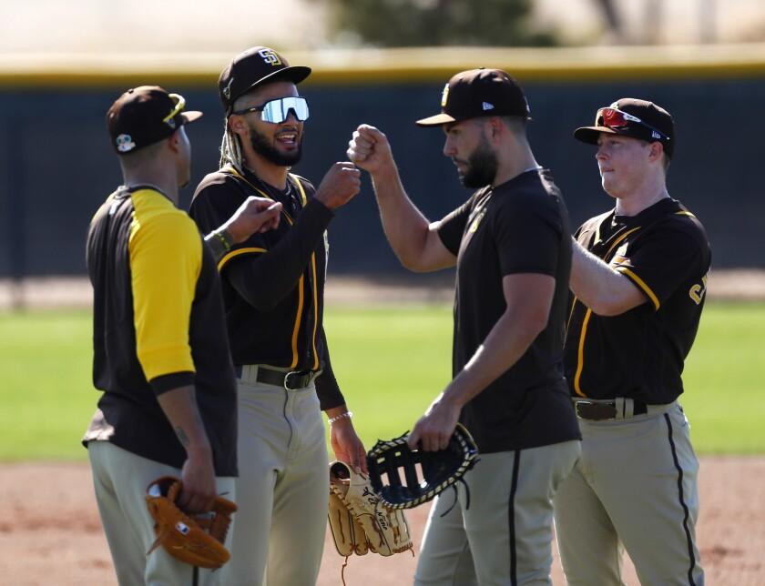 The Padres' Manny Machado, left, Fernando Tatis Jr., Eric Hosmer, and Jake Cronenworth