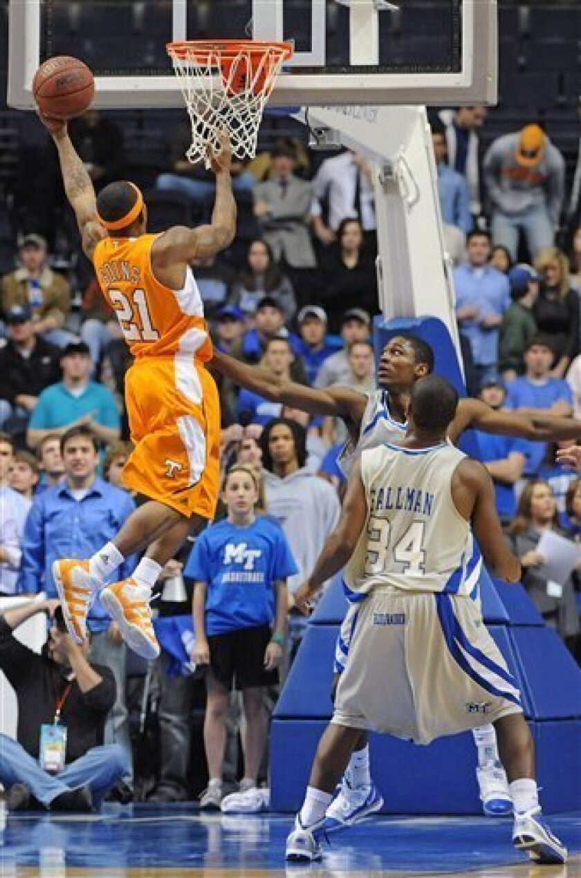 Tennessee guard Melvin Goins (21) jumps over the defense of Middle Tennessee forward J.T. Sulton and guard James Gallman (34) in the first half of an NCAA college basketball game in Nashville, Tenn., Friday, Dec. 11, 2009. (AP Photo/Frederick Breedon)