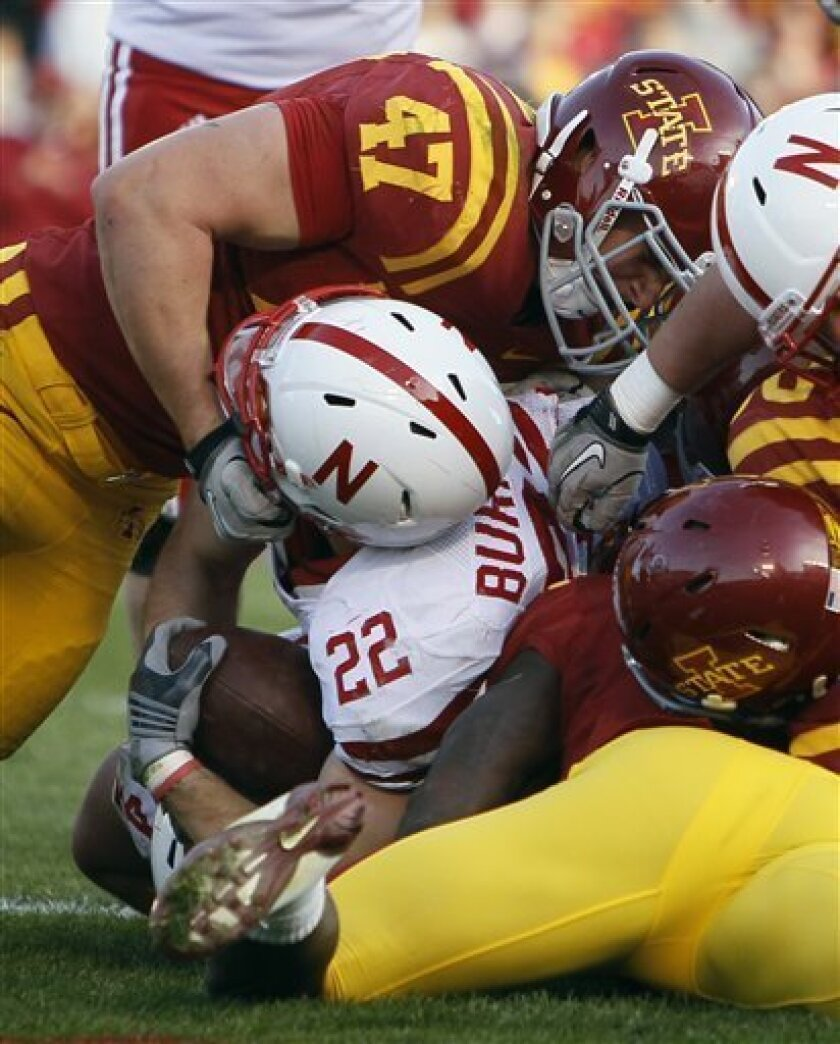 Nebraska running back Rex Burkhead (22) has his helmet grabbed by Iowa State linebacker A.J. Klein while scoring a touchdown during the second half of an NCAA college football game, Saturday, Nov. 6, 2010, in Ames, Iowa. Nebraska won 31-30 in overtime. (AP Photo/Charlie Neibergall)