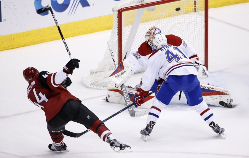 Arizona Coyotes' Kevin Connauton, left, sends the puck past Montreal Canadiens goalie Mike Condon and Paul Byron (41) for a score during the second period of an NHL hockey game Monday, Feb. 15, 2016, in Glendale, Ariz. (AP Photo/Ross D. Franklin)