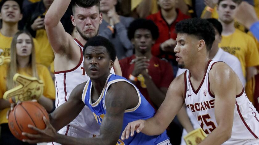 LOS ANGELES, CALIF. - JAN. 19, 2019. UCLA guard Kris Wilkes gets boxed in by USC defenders Mick Rak