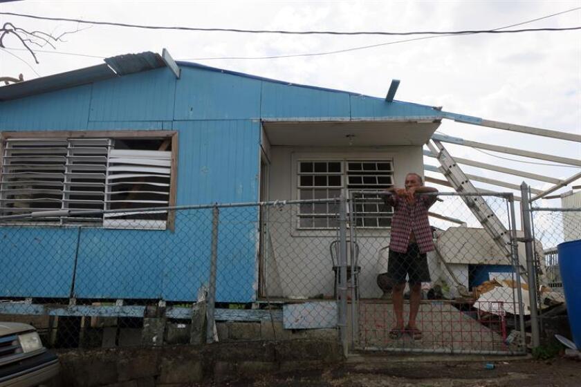 Un habitante observa las operaciones militares para la recuperación de Puerto Rico, desde la reja de su vivienda, el viernes 6 de octubre de 2017, en Canóvanas, (Puerto Rico). EFE/Archivo