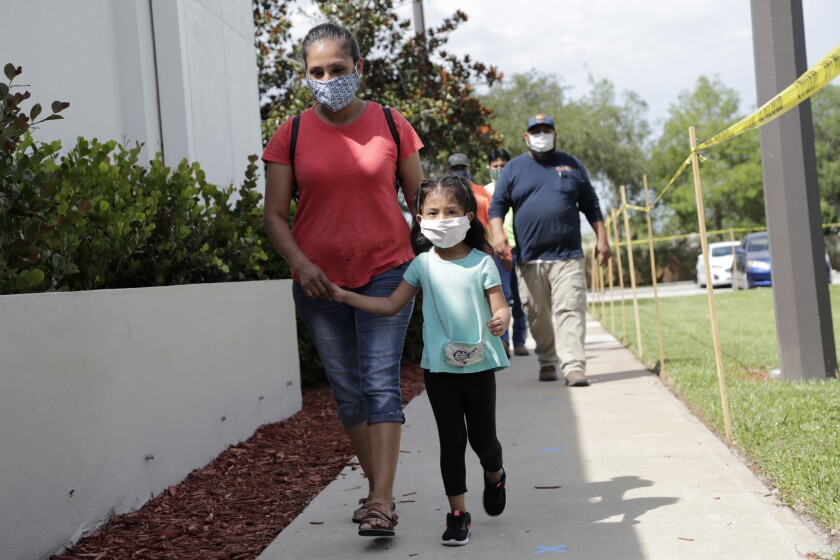 Flora Garcia arrives with her daughter Krislaya Trejo at the Florida Department of Health in Collier County