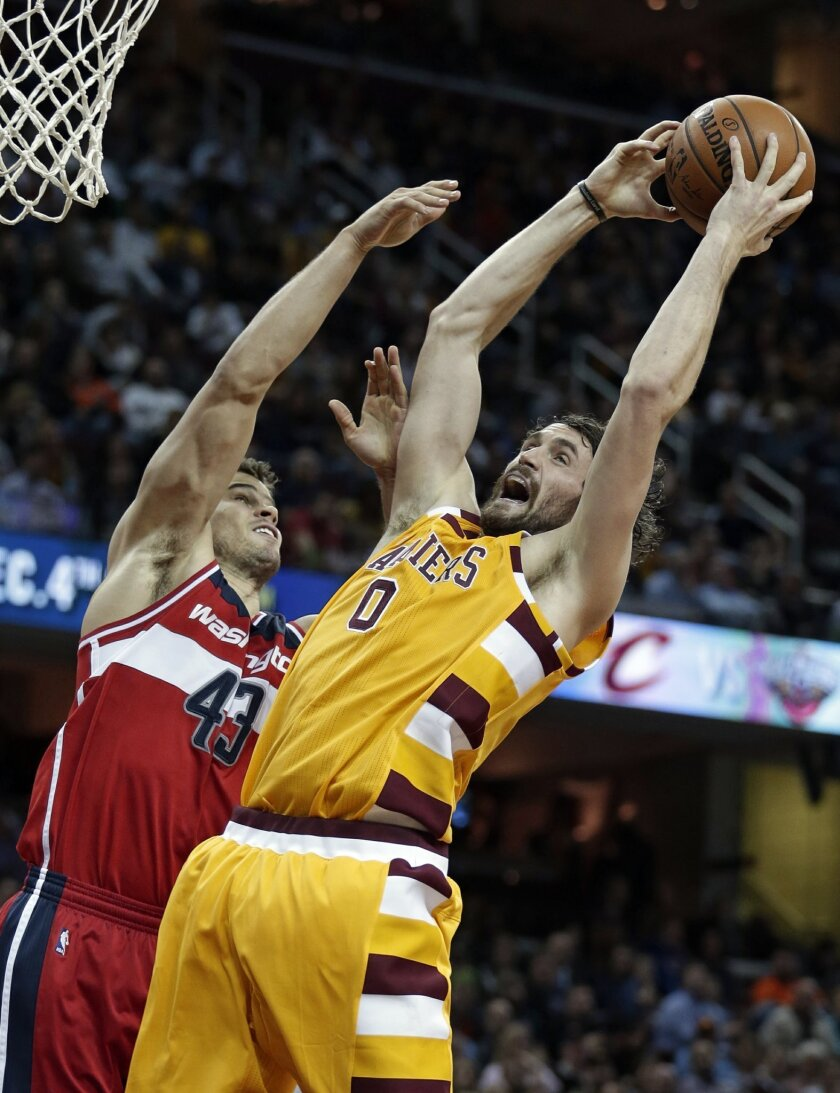FILE - In this Dec. 1, 2015, file photo, Cleveland Cavaliers' Kevin Love (0) grabs a rebound ahead of Washington Wizards' Kris Humphries (43) in the second half of an NBA basketball game, Cleveland. The Cleveland forward has heard his name in trade rumors for much of the season.  (AP Photo/Tony Dej