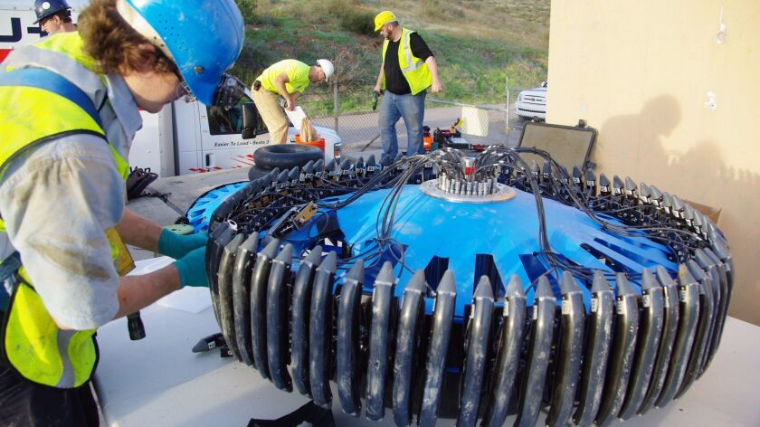 Workers from the San Diego County Water Authority install an the electromagnetic assessment tool in a pipeline in Lakeside.