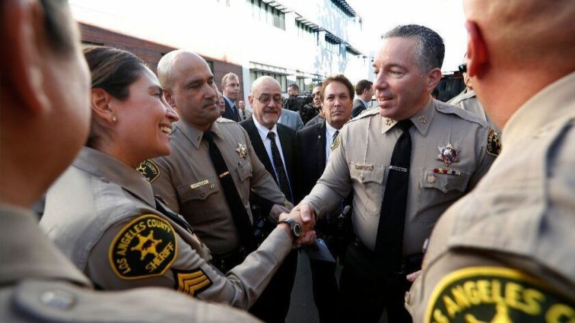 Sheriff Alex Villanueva, right, greets deputies after his swearing-in ceremony at East Los Angeles College on Dec. 3.