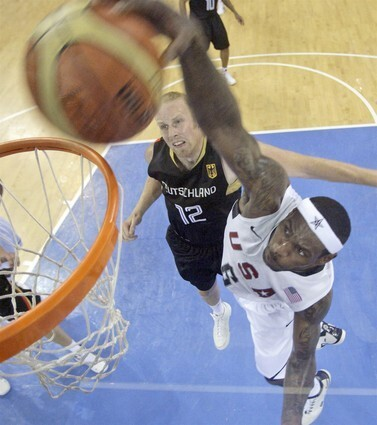 USA's LeBron James and Cleveland Cavalier star dunks as Gemany and Los Angeles Clipper center Chris Kaman looks on.