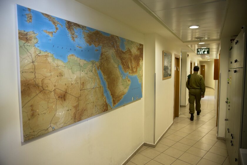 """In this photo taken Wednesday, Feb. 9, 2016, an Israeli soldier walks in an office in downtown Tel Aviv. A military program called """"seeing into the distance,"""" provides training and assistance to Israelis on the autism spectrum who wish to enlist in the military. (AP Photo/Sebastian Scheiner)"""
