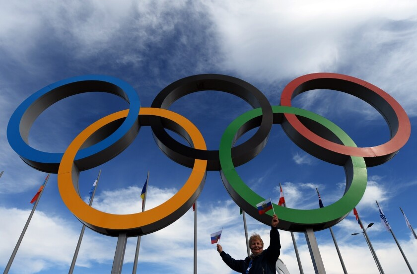 A woman poses under the Olympic rings during the Winter Games in Sochi, Russia.