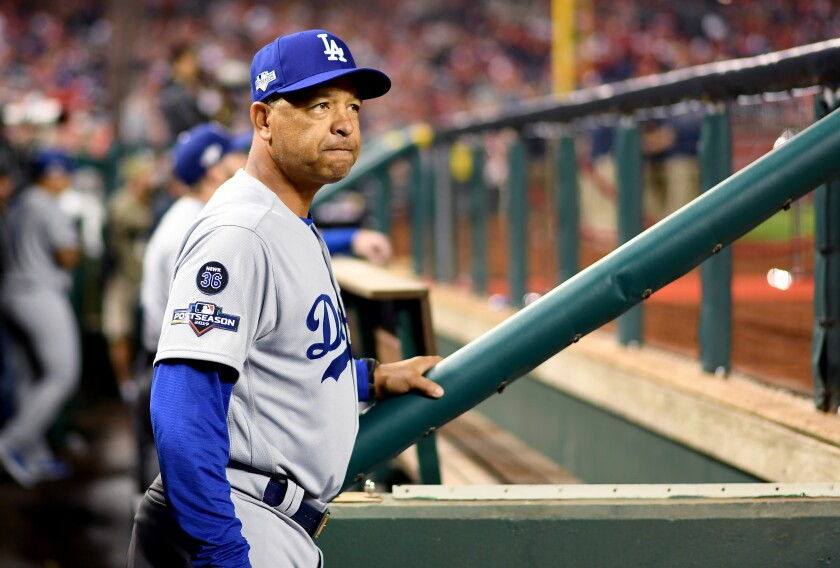 Dodgers manager Dave Roberts stands in the dugout before Game 3 of the NLDS at Nationals Park.