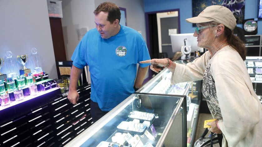 Grant Palmer, left, helps Hope Parks with purchases at the Canna Cruz medical cannabis dispensary in Santa Cruz, Calif.