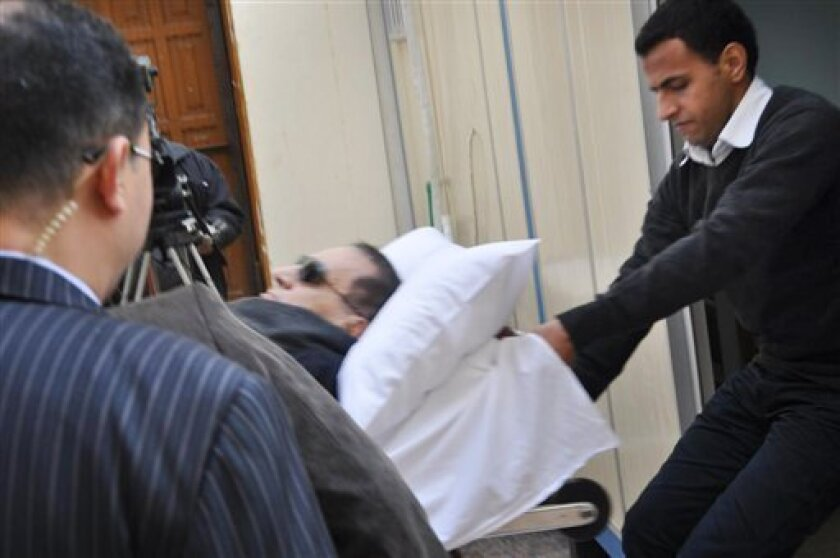 Former Egyptian president Hosni Mubarak is seen lying on a gurney bed at the court house in Cairo, Egypt, Monday, Jan. 2, 2012. The trial of Hosni Mubarak has resumed amid speculation that a recent acquittal of policemen tried for killing Egyptian protesters could be a prelude to the dismissal of charges against the ousted leader. Mubarak faces charges of complicity in the killing of more than 800 protesters during last year's uprising that toppled his regime. (AP Photo/Mohammed al-Law)