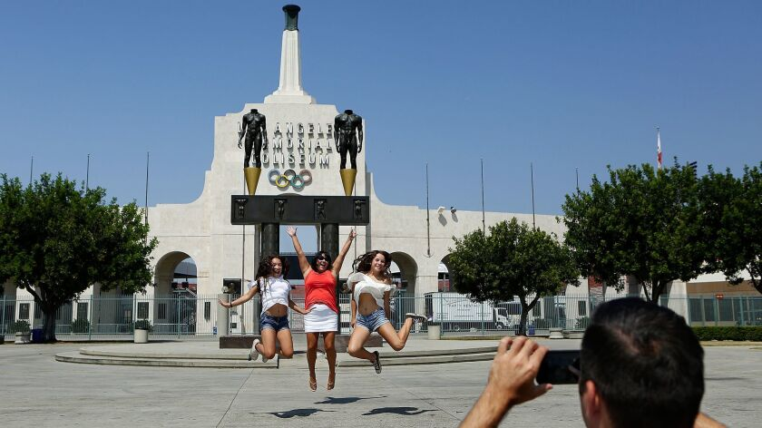 Visitors take pictures outside the Los Angeles Memorial Coliseum.
