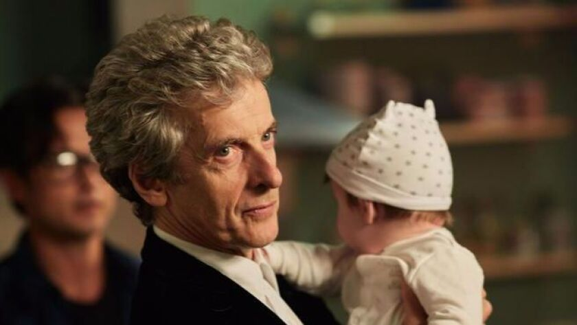 """Peter Capaldi as the Doctor minds a baby in a 2016 episode of """"Doctor Who."""" Capaldi has announced hi"""