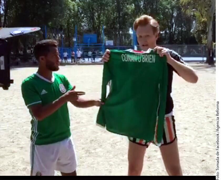 El delantero del Galaxy de Los Ángeles Giovani dos Santos (izq.) entregó al presentador Conan O'Brien (der.), quien se encuentra en la Ciudad, una camiseta de la Selección Mexicana.