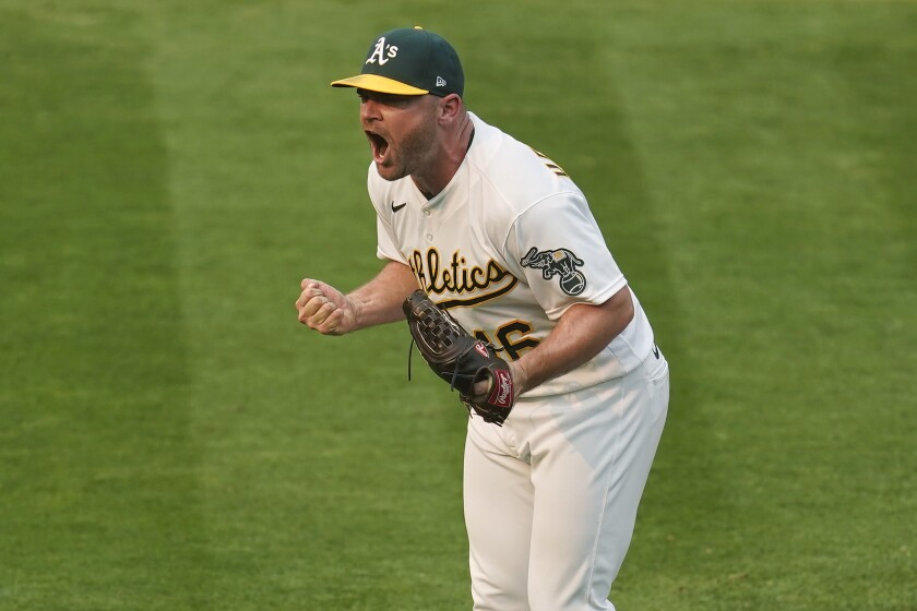 Oakland Athletics relief pitcher Liam Hendriks celebrates after striking out Chicago White Sox's Nomar Mazara.