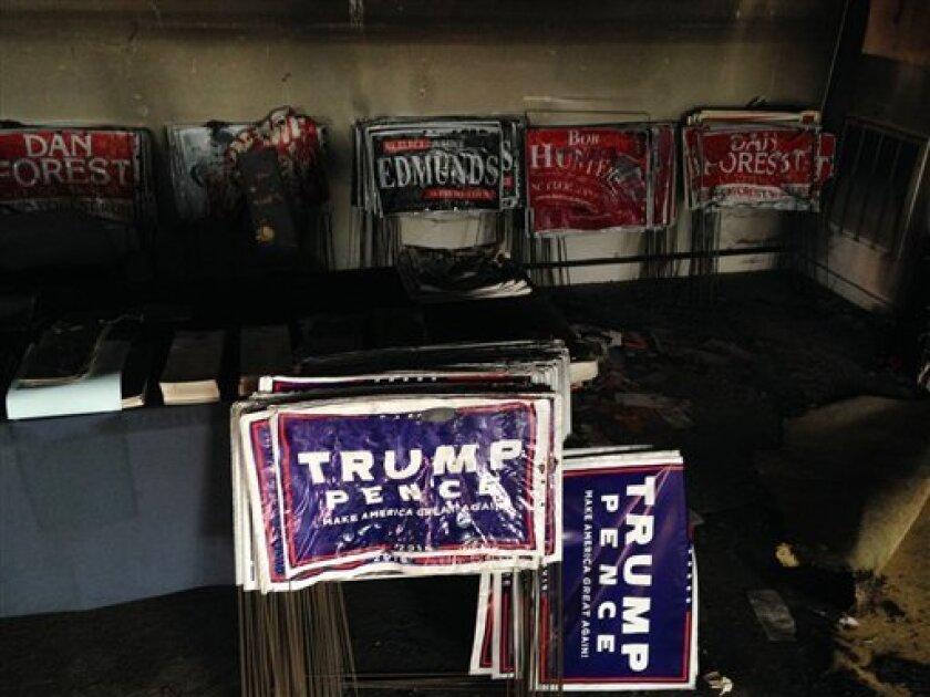 """Varios carteles de campaña se derritieron durante un incendio intencional en la oficina del Partido Republicano en Hillsborough, North Carolina, el domingo 16 de octubre de 2016. Alguien lanzó durante la noche una botella con líquido inflamable por una ventana al interior del lugar, hubo daños pero no víctimas, según las autoridades. También fue pintada una pared contigua con una frase dirigida contra esa fuerza política en la que se mencionaba a """"republicanos nazis"""", de acuerdo con las autoridades."""