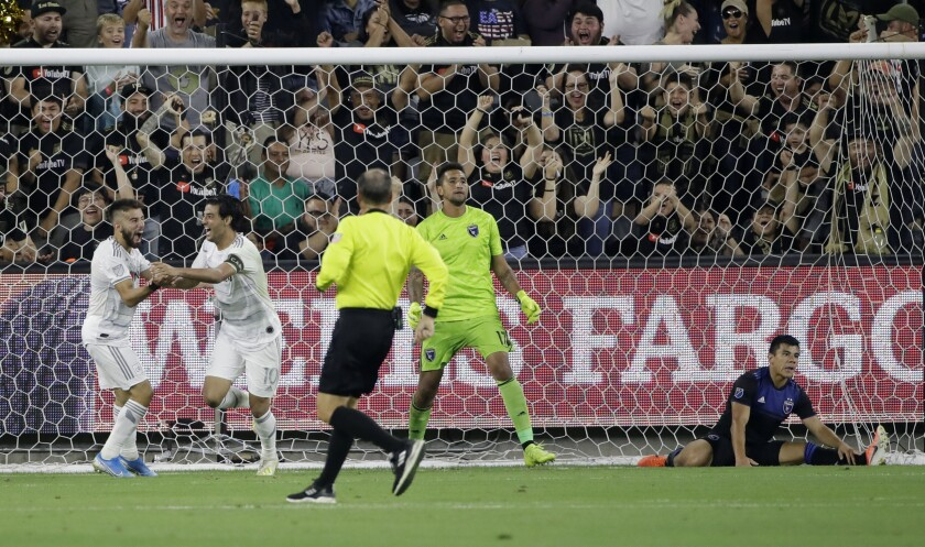 LAFC forward Carlos Vela, second from left, celebrates with teammate Diego Rossi, left, after scoring past San Jose  goalkeeper Daniel Vega and defender Nick Lima.