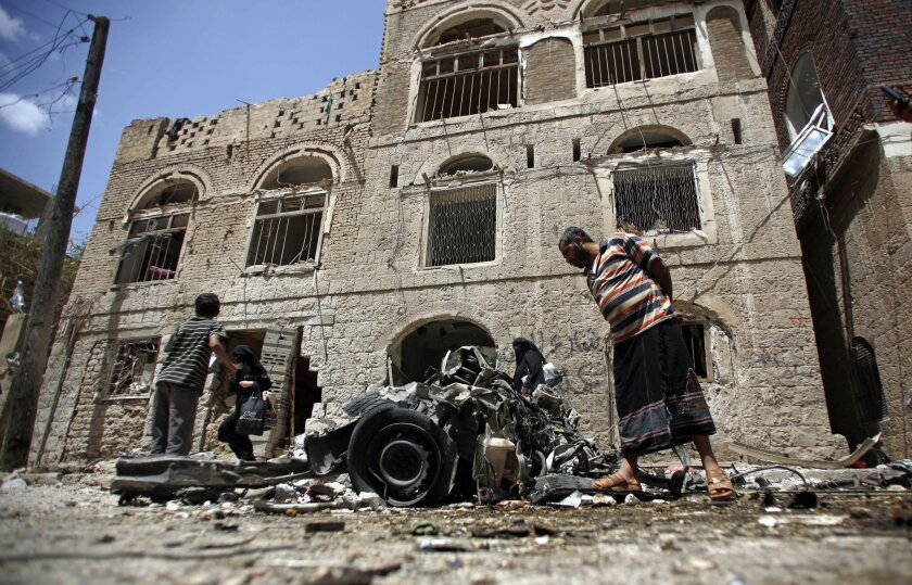 FILE - In this Tuesday, June 30, 2015 file photo, People stand amid wreckage of a vehicle at the site of a car bomb attack near a military hospital in Sanaa, Yemen. The World Health Organization says nearly 1,000 people have been killed worldwide in attacks on medical facilities in conflicts over t