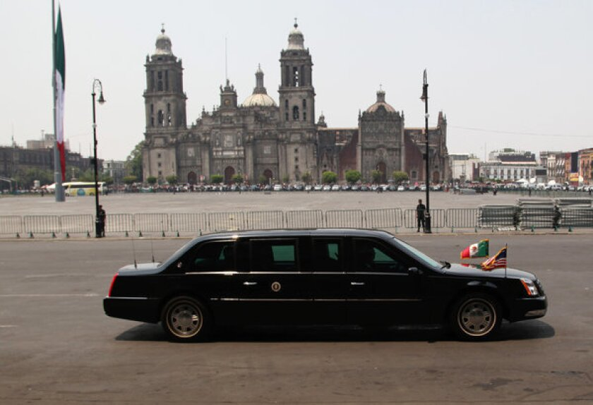 """Obama's presidential limousine, nicknamed """"The Beast,"""" is driven past the Metropolitan Cathedral in Mexico City on Thursday."""