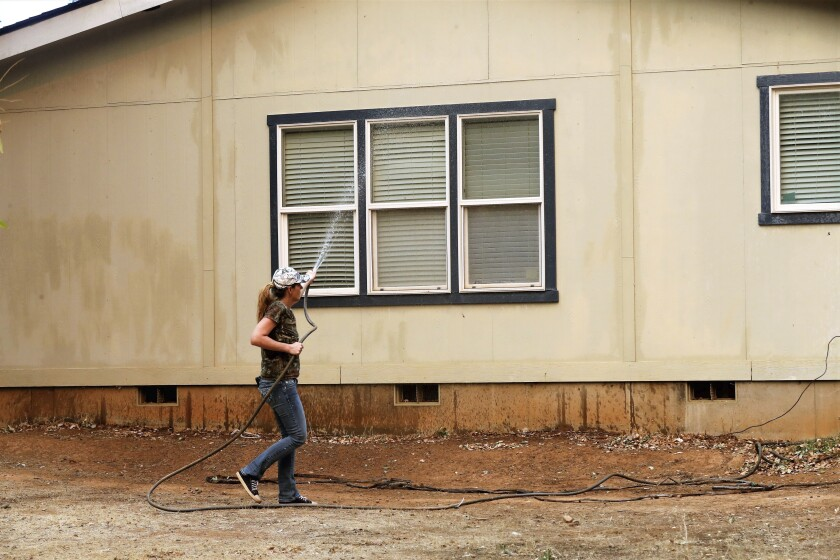 Katie Wright hoses down a family home on Casa Drive in an evacuated neighborhood about a half-mile from the Fawn Fire near Redding, Calif., on Thursday, Sept. 23, 2021. Evacuations have been ordered in a Northern California community as a new wildfire spreads. (Mike Chapman/The Record Searchlight via AP)