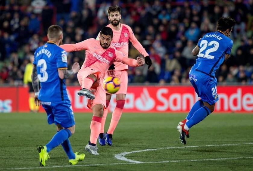 El delantero uruguayo del FC Barcelona, Luis Suárez (c), dispara a puerta y anota un gol ante el Getafe CF, el segundo del equipo en el partido de la 18? jornada de Liga en Primera División que se jugó en el Coliseum Alfonso Pérez, en Getafe. EFE