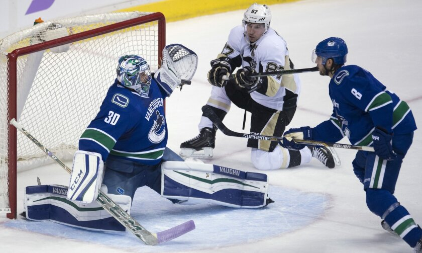 Vancouver Canucks defenseman Chris Tanev, right, looks on as Pittsburgh Penguins center Sidney Crosby, center, tries to get a shot past Vancouver Canucks goalie Ryan Miller (30) during the second period of an NHL hockey game Wednesday, Nov. 4, 2015, in Vancouver, British Columbia. (Jonathan Hayward