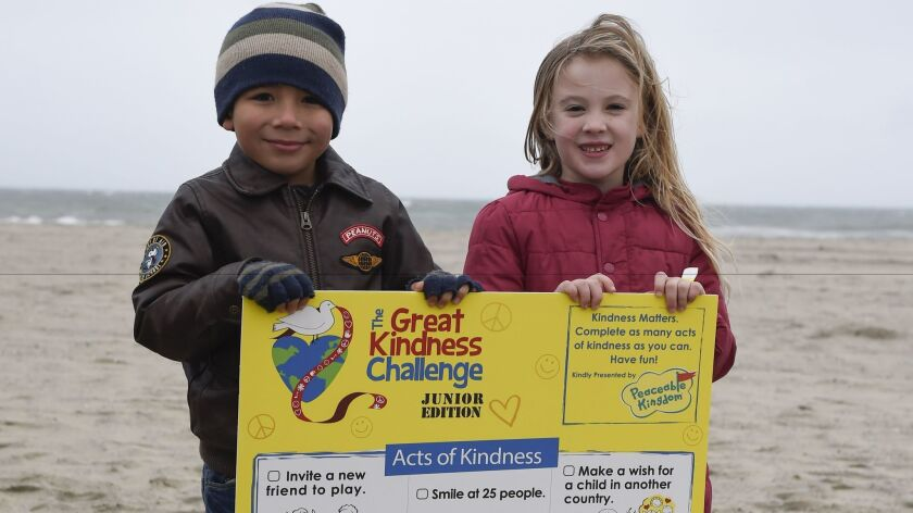Kids pose on the Carlsbad beach with a poster promoting the junior edition checklist of The Great Kindness Challenge activities.