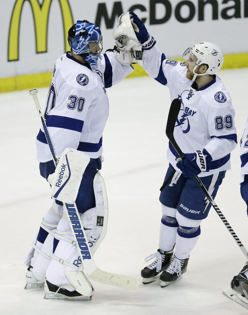 Tampa Bay Lightning goalie Ben Bishop (30) is congratulated by teammate defenseman Nikita Nesterov after their 5-2 win over the Detroit Red Wings in Game 6 of a first-round NHL Stanley Cup hockey playoff series, Monday, April 27, 2015 in Detroit. (AP Photo/Carlos Osorio)