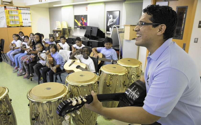 Music teacher Bladimir Castro demonstrates guitar during his class at Carlos Santana Arts Academy in North Hills. The campus is abuzz with visual and performing arts, but the principal has gone outside the school district for help.